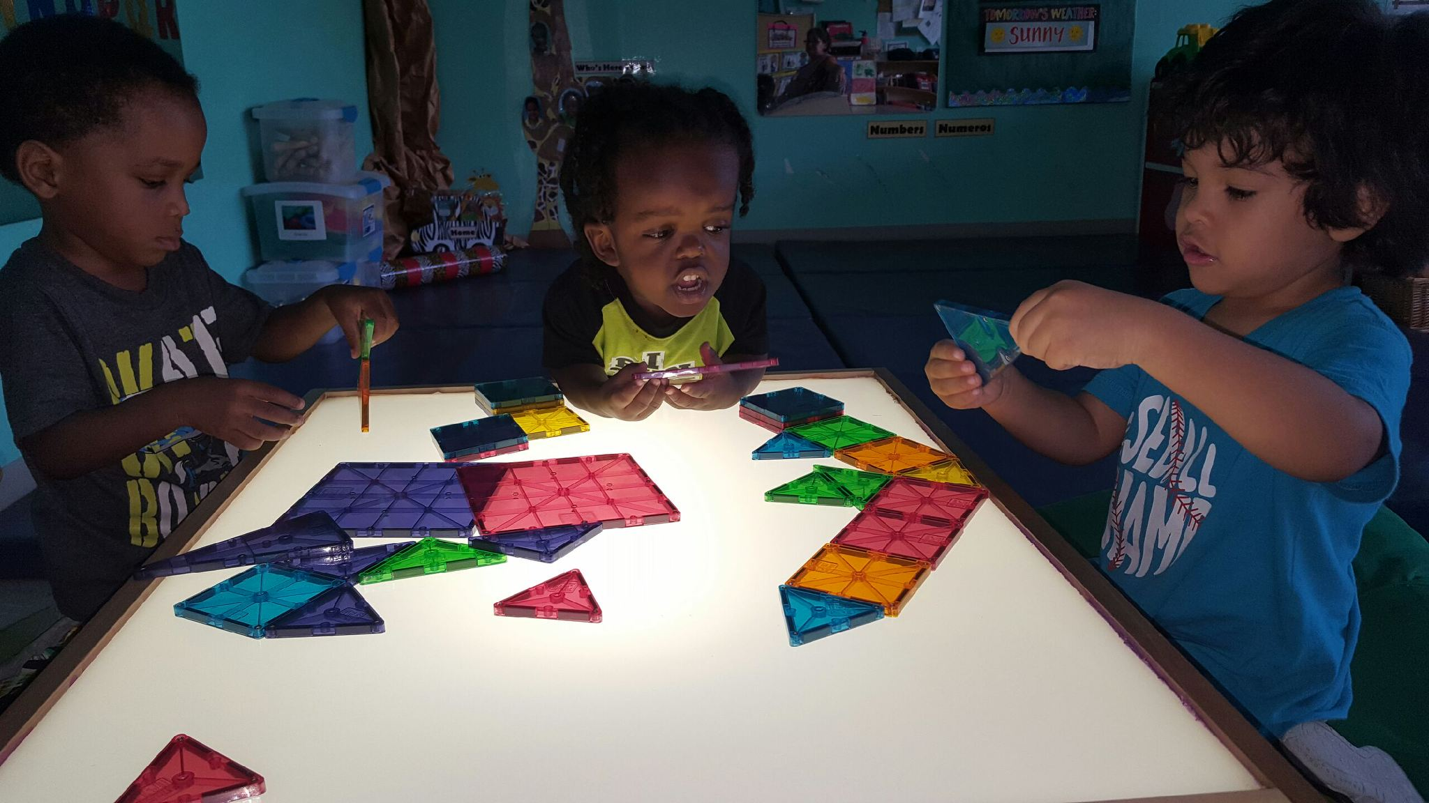 Children using a light table and shapes